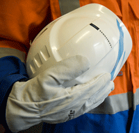Photo of staff member in PPE gear holding helmet